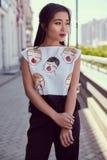 Πανέμορφη ασιατική γυναίκα στο φόρεμα μόδας που περπατά κατά μήκος της φωτεινής οδού Στοκ Εικόνες