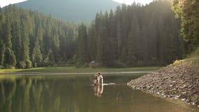 Πανέμορφη γοργόνα από τη λίμνη στα ξύλα που καλούν το άτομο για να πάει με την στο νερό Μαγική έννοια φαντασίας φιλμ μικρού μήκους