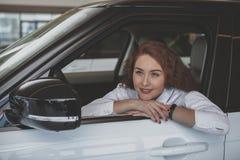 Πανέμορφη γυναίκα που αγοράζει το νέο αυτοκίνητο στον αντιπρόσωπο στοκ εικόνες