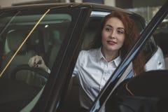 Πανέμορφη γυναίκα που αγοράζει το νέο αυτοκίνητο στον αντιπρόσωπο στοκ εικόνα