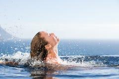 Πανέμορφη γυναίκα που αυξάνει το κεφάλι της από το νερό Στοκ Εικόνες
