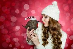 Πανέμορφη γυναίκα που κρατά ένα χαριτωμένο πουλί παιχνιδιών με το καπέλο santa Ασυνήθιστη αστεία έννοια Χριστουγέννων με το υπόβα Στοκ Εικόνες