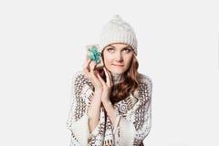 Πανέμορφη γυναίκα που κρατά το μικροσκοπικό παρόν, έννοια Χριστουγέννων περιέργειας Στοκ Εικόνες