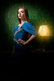 Πανέμορφη γυναίκα στο μπλε φόρεμα στο εκλεκτής ποιότητας δωμάτιο Στοκ Εικόνες
