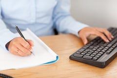 Πανέμορφη επιχειρηματίας που δακτυλογραφεί και που γράφει στοκ εικόνες με δικαίωμα ελεύθερης χρήσης