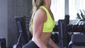 Πανέμορφη εύθυμη φίλαθλος που κάνει την άσκηση δικέφαλων μυών στη γυμναστική φιλμ μικρού μήκους