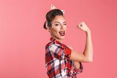 Πανέμορφη ισχυρή νέα καρφίτσα-επάνω γυναίκα που παρουσιάζει δικέφαλους μυς στοκ φωτογραφία
