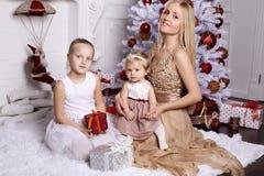 Πανέμορφη μητέρα με τη μακροχρόνια τοποθέτηση ξανθών μαλλιών με το λατρευτό χαριτωμένο δ Στοκ Φωτογραφία