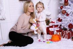 Πανέμορφη μητέρα με τη μακροχρόνια τοποθέτηση ξανθών μαλλιών με το λατρευτό χαριτωμένο δ Στοκ Φωτογραφίες