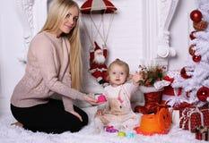 Πανέμορφη μητέρα με τη μακροχρόνια τοποθέτηση ξανθών μαλλιών με το λατρευτό χαριτωμένο δ Στοκ Εικόνες