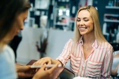 Πανέμορφη νέα γυναίκα που παίρνει τα καρφιά της γίνοντα από έναν μανικιουρίστα στοκ εικόνα με δικαίωμα ελεύθερης χρήσης