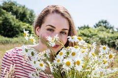 Πανέμορφη νέα γυναίκα που χαμογελά με camomile τα λουλούδια για τη φυσική ομορφιά Στοκ Φωτογραφίες