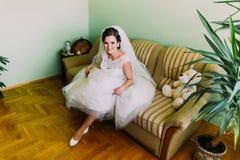 Πανέμορφη νέα συνεδρίαση νυφών στον καναπέ που παρουσιάζει πόδια της με τα μοντέρνα άσπρα παπούτσια Στοκ Φωτογραφίες