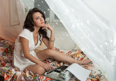 Πανέμορφη νέα συνεδρίαση συγγραφέων brunette στο κρεβάτι στοκ φωτογραφία