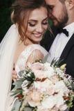 Πανέμορφη νύφη και μοντέρνος νεόνυμφος που αγκαλιάζουν και που χαμογελούν ήπια στο β στοκ εικόνες