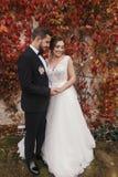 Πανέμορφη νύφη και μοντέρνος νεόνυμφος που αγκαλιάζουν και που χαμογελούν ήπια στο W στοκ εικόνα με δικαίωμα ελεύθερης χρήσης