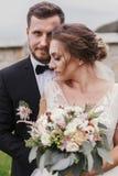 Πανέμορφη νύφη με τη σύγχρονη ανθοδέσμη και μοντέρνος νεόνυμφος hugg ήπια στοκ εικόνες