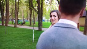 Πανέμορφη νύφη που χαμογελά και που περπατά γύρω από το νεόνυμφο που στέκεται ακόμα στο ηλιόλουστο πάρκο απόθεμα βίντεο