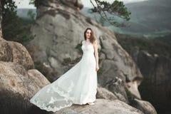 Πανέμορφη νύφη στην κομψή τοποθέτηση ανθοδεσμών εκμετάλλευσης φορεμάτων κοντά στο δάσος Στοκ Φωτογραφία