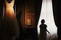 Πανέμορφη σκιαγραφία νυφών που στέκεται στο μοντέρνο γαμήλιο φόρεμα, han στοκ φωτογραφία