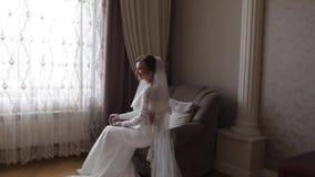 Πανέμορφη συνεδρίαση νυφών στην καρέκλα στο σπίτι Όμορφη γυναίκα στο γαμήλιο φόρεμα φιλμ μικρού μήκους