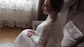 Πανέμορφη συνεδρίαση νυφών στην καρέκλα στο σπίτι Όμορφη γυναίκα στο γαμήλιο φόρεμα απόθεμα βίντεο