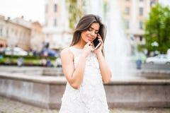 Πανέμορφη όμορφη νέα γυναίκα brunette που μιλά στο έξυπνος-τηλέφωνο στο υπόβαθρο οδών πόλεων στοκ φωτογραφίες