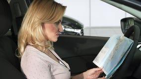 Πανέμορφη ώριμη γυναίκα που εξετάζει τη συνεδρίαση χαρτών σε ένα αυτοκίνητο απόθεμα βίντεο