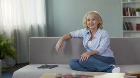 Πανέμορφη ώριμη θηλυκή συνεδρίαση στον καναπέ και να εξετάσει τη κάμερα, διαφήμιση απόθεμα βίντεο