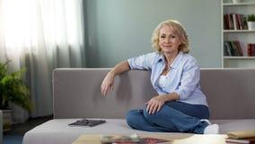 Πανέμορφη ώριμη θηλυκή συνεδρίαση στον καναπέ και να εξετάσει τη κάμερα, διαφήμιση στοκ εικόνες