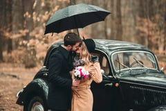 Πανέμορφος η τοποθέτηση νυφών και νεόνυμφων στο δάσος πεύκων κοντά στο αναδρομικό αυτοκίνητο στη ημέρα γάμου τους Στοκ Φωτογραφία