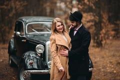 Πανέμορφος η τοποθέτηση νυφών και νεόνυμφων στο δάσος πεύκων κοντά στο αναδρομικό αυτοκίνητο στη ημέρα γάμου τους Στοκ Φωτογραφίες