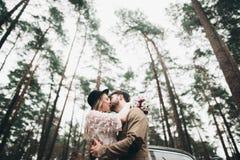 Πανέμορφος η τοποθέτηση νυφών και νεόνυμφων στο δάσος πεύκων κοντά στο αναδρομικό αυτοκίνητο στη ημέρα γάμου τους Στοκ εικόνες με δικαίωμα ελεύθερης χρήσης