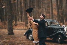 Πανέμορφος η τοποθέτηση νυφών και νεόνυμφων στο δάσος πεύκων κοντά στο αναδρομικό αυτοκίνητο στη ημέρα γάμου τους Στοκ Εικόνες