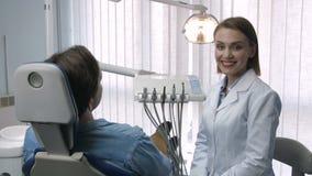 Πανέμορφος θηλυκός οδοντίατρος που χαμογελά στη κάμερα φιλμ μικρού μήκους