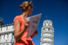 Πανέμορφος θηλυκός τουρίστας με το χάρτη που θαυμάζει τον κλίνοντας πύργο στοκ εικόνα