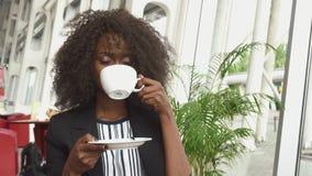 Πανέμορφος καφές κατανάλωσης επιχειρησιακής κυρίας αφροαμερικάνων στον αερολιμένα περιμένοντας μια πτήση απόθεμα βίντεο