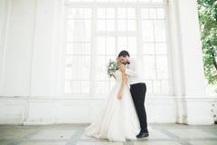 Πανέμορφος νεόνυμφος που αγκαλιάζει ήπια τη μοντέρνη νύφη Αισθησιακή στιγμή του γαμήλιου ζεύγους πολυτέλειας στοκ εικόνα