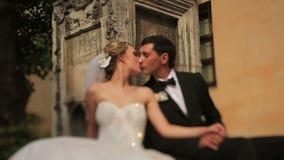 Πανέμορφος ξανθός η νύφη και το όμορφο φίλημα νεόνυμφων μπροστά από το παλαιό μπαρόκ κτήριο σε Lviv Ηλιόλουστη ημέρα γάμου απόθεμα βίντεο