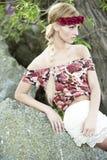 Πανέμορφος ξανθός στην κόκκινη κορώνα λουλουδιών στοκ φωτογραφίες
