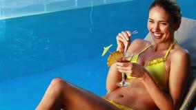 Πανέμορφος ξανθός στο μπικίνι που απολαμβάνει ένα poolside κοκτέιλ απόθεμα βίντεο