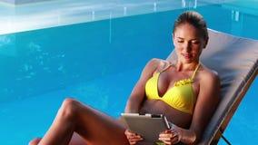 Πανέμορφος ξανθός στο μπικίνι που βρίσκεται στο poolside deckchair χρησιμοποιώντας το PC ταμπλετών φιλμ μικρού μήκους