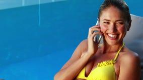 Πανέμορφος ξανθός στο μπικίνι που κουβεντιάζει στο τηλεφωνικό poolside απόθεμα βίντεο