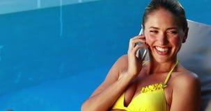 Πανέμορφος ξανθός στο μπικίνι που κουβεντιάζει στο τηλεφωνικό poolside φιλμ μικρού μήκους