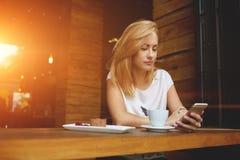 Πανέμορφο βίντεο προσοχής κοριτσιών hipster στο τηλέφωνο κυττάρων κατά τη διάρκεια του προγεύματος πρωινού στον καφέ στοκ φωτογραφία με δικαίωμα ελεύθερης χρήσης