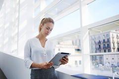 Πανέμορφο θηλυκό υπερήφανο CEO που αναλύει το πρόγραμμα για την ψηφιακή ταμπλέτα στοκ εικόνα