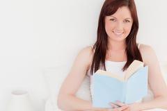 Πανέμορφο κοκκινομάλλες θηλυκό που διαβάζει ένα βιβλίο στοκ εικόνες