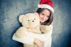 Πανέμορφο κορίτσι με τη teddy αρκούδα στενός κόκκινος χρόνος Χριστουγέννων ανασκόπησης επάνω Στοκ Φωτογραφίες