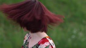 Πανέμορφο κορίτσι που τινάζει την κοκκινομάλλη επικεφαλής και εξέταση χαμόγελού της τη κάμερα φιλμ μικρού μήκους