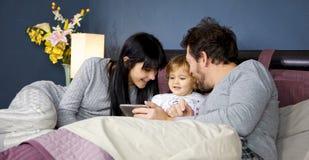 Πανέμορφο ξανθό μωρό με τον πατέρα και τη μητέρα στο κρεβάτι το πρωί στοκ φωτογραφίες